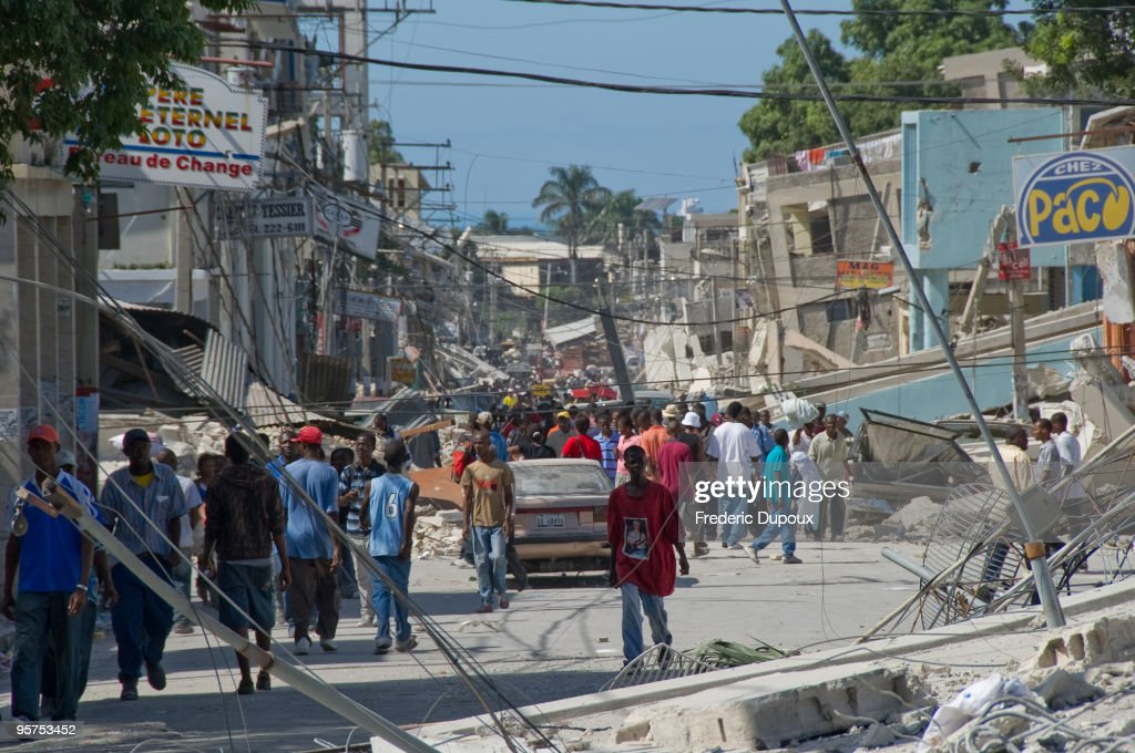 People wander the streets in front of the remains of a boarding school in the downtown area January 13 2010 in PortauPrince Haiti Planeloads of...