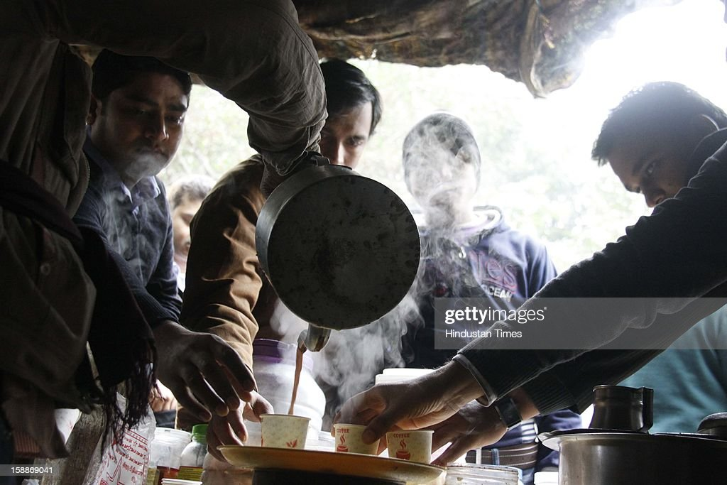 People warm themselves, having tea during a cold day, as temperature dips below 6 degree Celsius on January 2, 2013 in Gurgaon, India. There was no respite from cold and dense fog in North India as mercury dipped two degrees below normal to stay at 4.8 degree Celsius.