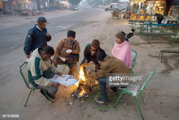 People warming up fire at bus stop, Jodhpur, Rajasthan, India
