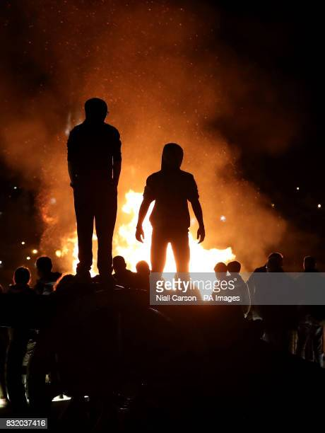 People watch a bonfire from the top of a cannon on Derry city walls in the bogside area of Londonderry which is traditionally torched on August 15 to...