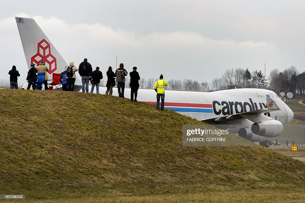 People watch a Cargolux Boeing 747 cargo aircraft landing on February 20, 2013 at Payerne airport. The Boeing will carry the Swiss sun-powered Solar Impulse HB-SIA prototype aircraft to San Francisco for a series of flights across the US from the West coast to the East Coast. AFP PHOTO / FABRICE COFFRINI