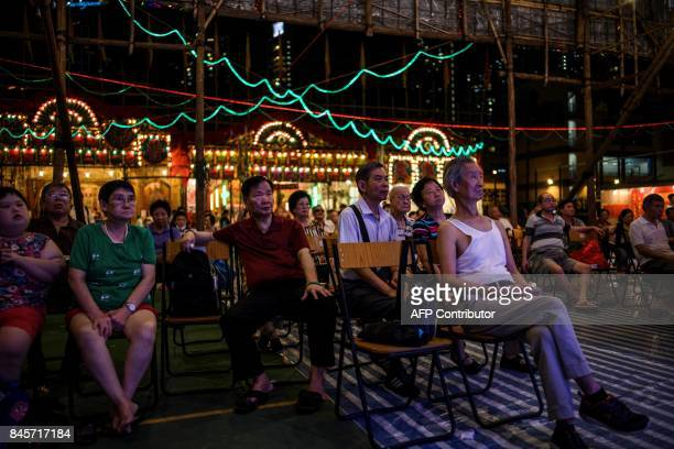 People watch a Chiu Chow opera performance during an event to mark the Hungry Ghost Festival in Hong Kong on September 11 2017 The festival...