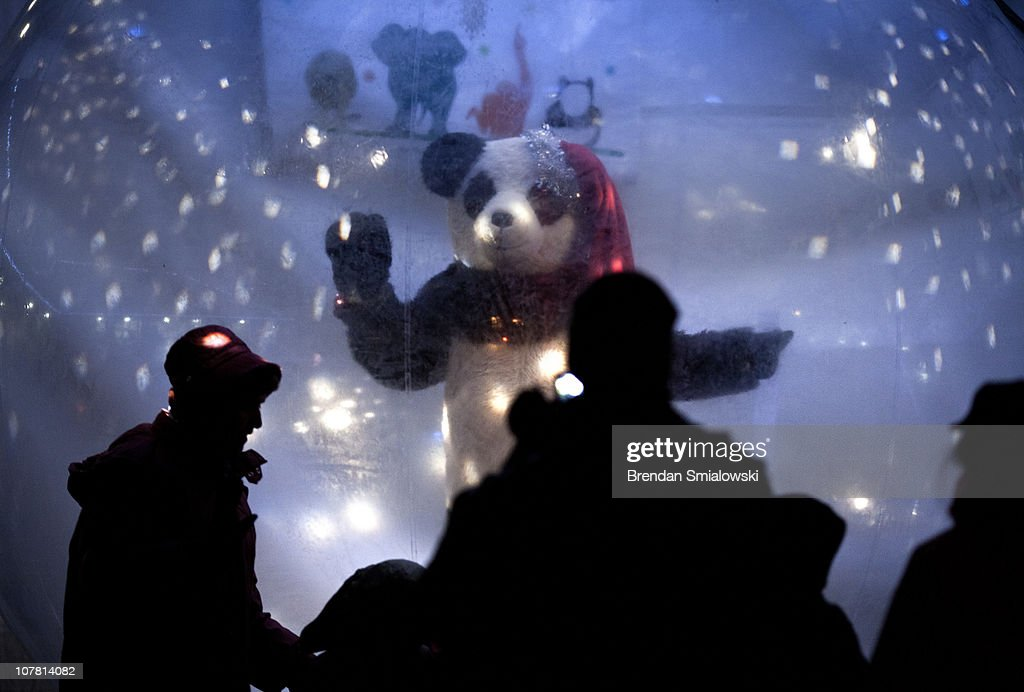 People watch a dancing panda bear at the Smithsonian's National Zoo December 29, 2010 in Washington, DC. The National Zoo decorated its main walk with holiday lights and other decorations for its yearly Zoo Lights celebration.