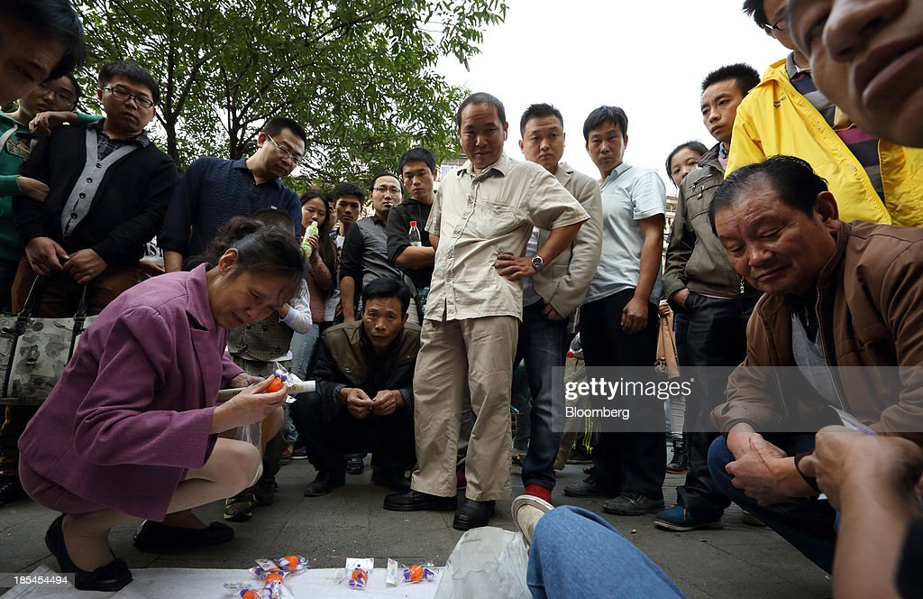 People watch a demonstration of a product by a street vendor in Wuhan, China, on Sunday, Oct. 20, 2013. China's economic expansion accelerated to 7.8 percent in the third quarter from a year earlier, the statistics bureau said Oct. 18, reversing a slowdown that put the government at risk of missing its 7.5 percent growth target for 2013. Photographer: Tomohiro Ohsumi/Bloomberg via Getty Images