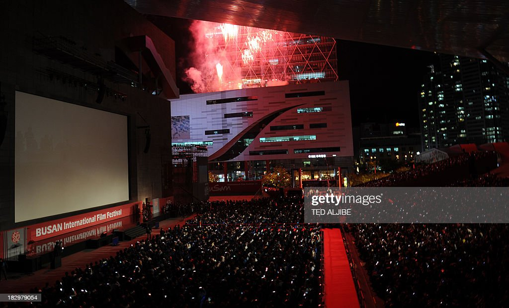 People watch a firework display during the opening ceremony of the 18th Busan International Film Festival (BIFF) in Busan on October 3, 2013. Stars of Asian cinema gathered in the South Korean port city of Busan October 3, for the opening of the region's biggest film festival, showcasing new talent in a region where box office takings will soon outstrip North America. AFP PHOTO/TED ALJIBE