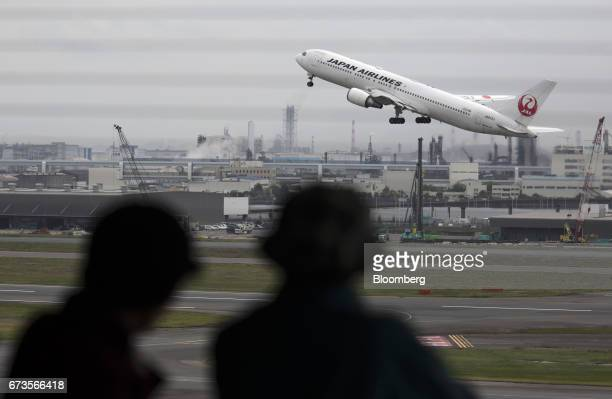 People watch a Japan Airlines Co aircraft taking off at Haneda Airport in Tokyo Japan on Wednesday April 26 2017 JAL is scheduled to release...