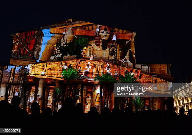 People watch a light show projected on the facade of the Bolshoi Theatre in Moscow on October 10 during the 'Circle of Light' Moscow International...