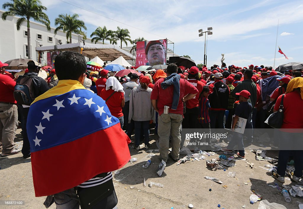 People watch a live broadcast of the funeral for Venezuelan President Hugo Chavez as a video of Chavez is played outside the Military Academy on March 8, 2013 in Caracas, Venezuela. Countless Venezuelans have paid their last respects to Chavez and more than 30 heads of state were expected to attend the funeral today.