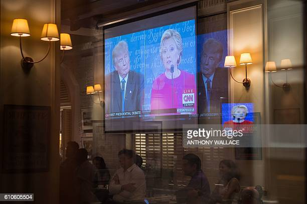 People watch a live projection in Hong Kong on September 27 2016 as Democratic nominee Hillary Clinton and Republican nominee Donald Trump take part...