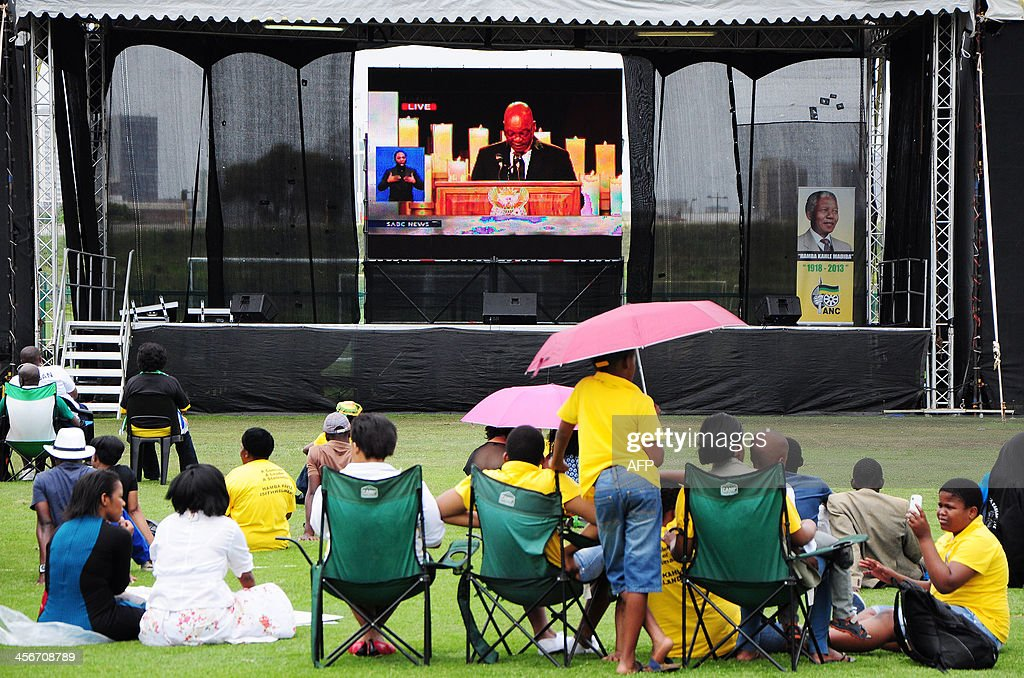 People watch a live television broadcast of the funeral ceremony for late former South African President Nelson Mandela, on the day of Mandela's burial in his hometown, on December 15, 2013, in Durban. Mandela was buried near his homestead Qunu today, ending 10 days of national mourning and global tributes for the prisoner-turned-president who transformed his country and inspired the world. AFP PHOTO / Anesh Debiky