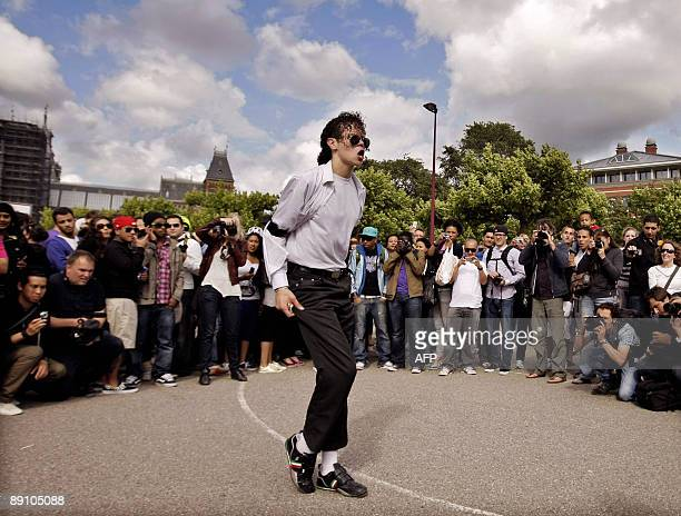 People watch a lookalike of US King of Pop Michael Jackson dancing on one of his hit 'Thriller' in the Museumpark on July 19 2009 in Amsterdam as...