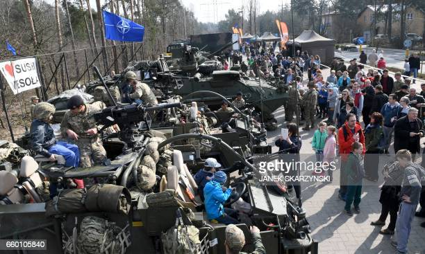 People watch a parade of US British and Romanian military equipment in the Wesola district of Polands capital Warsaw on March 29 2017 The troops will...