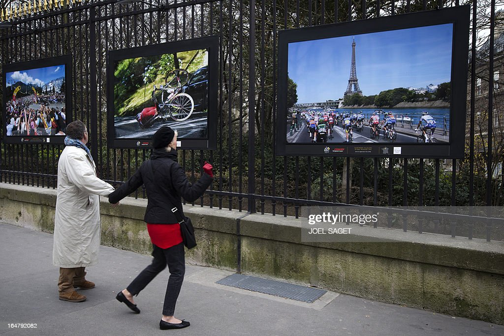 People watch a photo exhibition dedicated to the 100th anniversary of the Tour de France cycling race on the fences of the Luxembourg garden on March 28, 2013 in Paris.