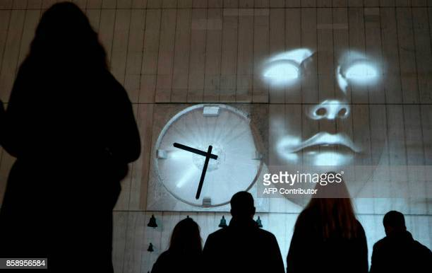 People watch a projection titled 'Room of a Nation' by Boris Vitazek on the wall of the Tesco department store in Bratislava during the White Night...