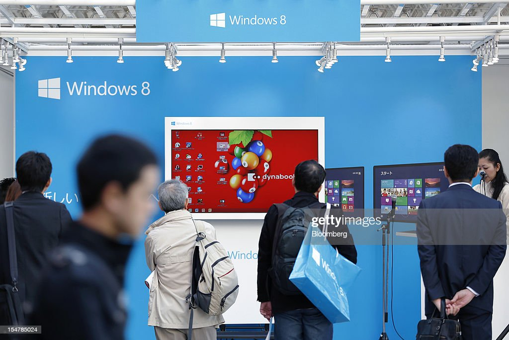 People watch a promotion for Microsoft Corp.'s Windows 8 operating system outside an electronics store in Tokyo, Japan, on Friday, Oct. 26, 2012. Microsoft introduced the biggest overhaul of its flagship Windows software in two decades, reflecting the rising stakes in its competition with Apple Inc. and Google Inc. for the loyalty of customers who are shunning personal computers and flocking to mobile devices. Photographer: Kiyoshi Ota/Bloomberg via Getty Images