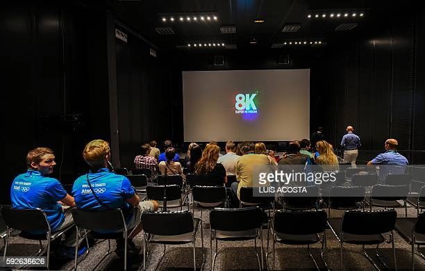 People watch a replay of the 100m race on a ultra high definition 8K screen inside the International Broadcast Center during the Olympic Games Rio...
