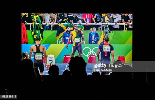 People watch a replay of the 110m race on a ultra high definition 8K screen inside the International Broadcast Center during the Olympic Games Rio...