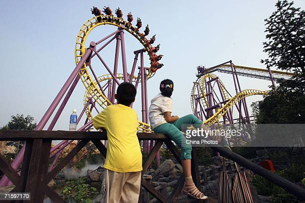 People watch a rollercoaster at Chinese Theme Park 'Happy Valley' on August 6 2006 in Beijing China Happy Valley the biggest theme park in China...