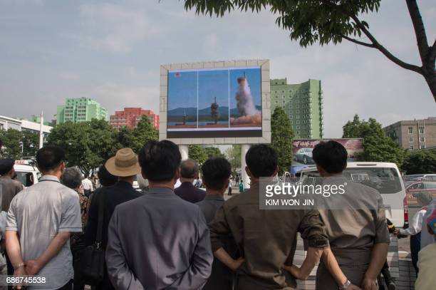 People watch a screen showing news coverage of the Pukguksong2 missile rocket launch at a public square in central Pyongyang on May 22 2017 North...