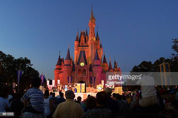 People watch a show on stage in front of Cinderella's castle at Walt Disney World's Magic Kingdom November 11 2001 in Orlando Florida