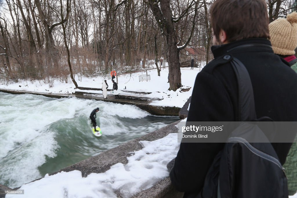 People watch a surfer riding the Eisbach wave on January 23, 2013 in Munich, Germany.