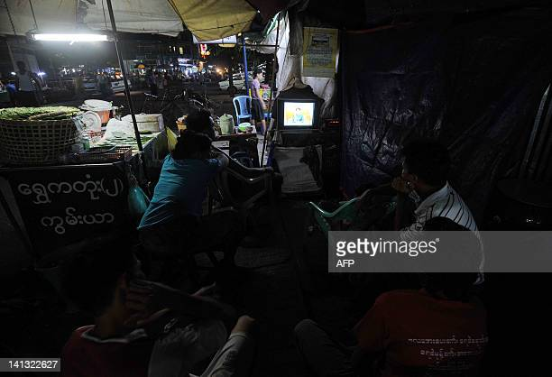 People watch a television broadcast of Myanmar opposition leader Aung San Suu Kyi's campaign speech in Yangon late on March 14 2012 Aung San Suu Kyi...