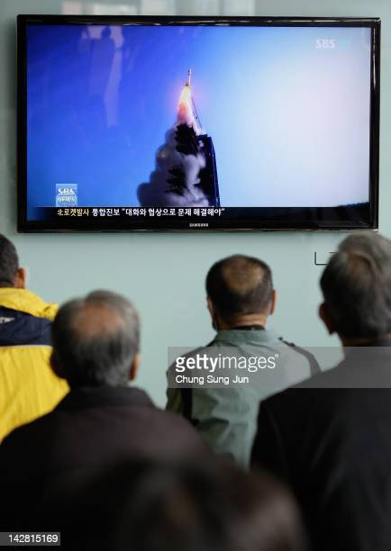 People watch a television broadcast reporting the North Korea launched the longrange missile at the Yongsan electronic market on April 13 2012 in...