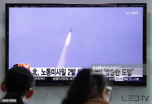 People watch a television broadcast reporting the North Korean missile launch at the Seoul Railway Station on March 26 2014 in Seoul South Korea...
