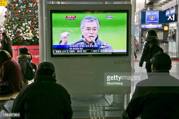 People watch a television broadcast showing Moon Jae In presidential candidate from the main opposition Democratic United Party at Seoul Station in...