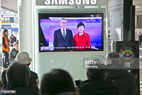 People watch a television broadcast showing South Korean presidential candidates Park Geun Hye from the ruling New Frontier Party right and Moon Jae...