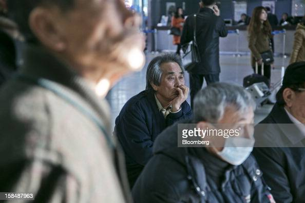 People watch a television broadcast showing South Korean presidential candidates Park Geun Hye from the ruling New Frontier Party and Moon Jae In...