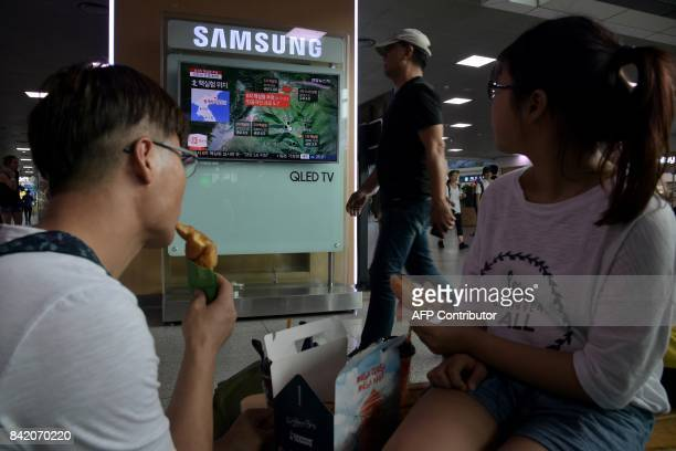 People watch a television display at a train station in Seoul on September 3 2017 showing a news broadcast about North Korea's latest possible...