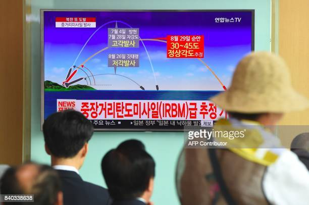 People watch a television news screen showing a graphic of a North Korean missile launch at a railway station in Seoul on August 29 2017 Nucleararmed...
