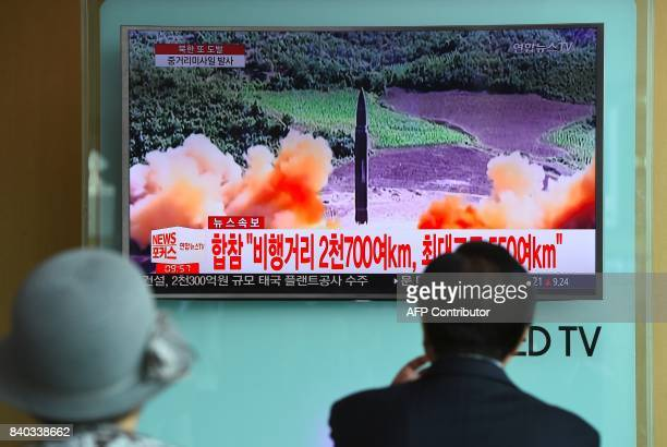 TOPSHOT People watch a television news screen showing file footage of a North Korean missile launch at a railway station in Seoul on August 29 2017...