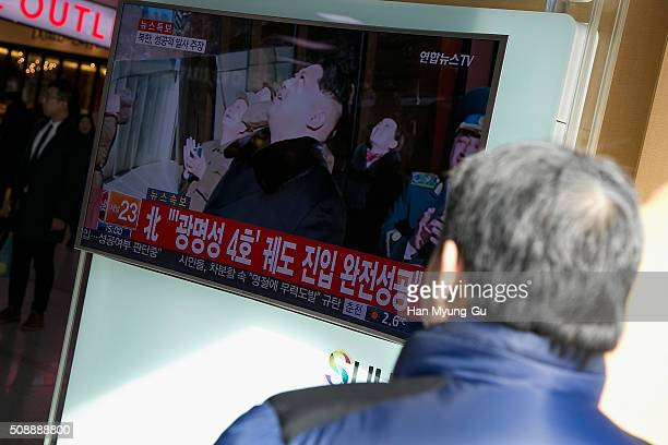 People watch a television screen showing a breaking news on North Korea's longrange rocket launch at Seoul Station on February 7 2016 in Seoul South...
