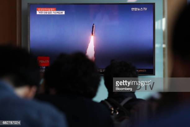 People watch a television screen showing a news broadcast on North Korea's ballistic missile launch at Seoul Station in Seoul South Korea on Sunday...