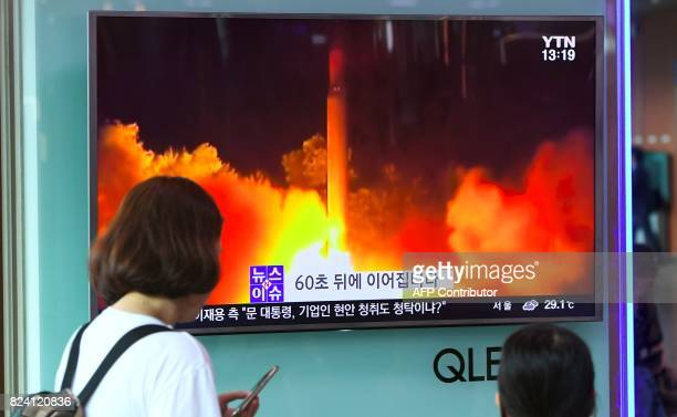 People watch a television screen showing a video footage of North Korea's latest test launch of an intercontinental ballistic missile at a railway...