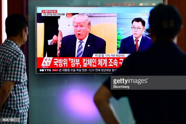 People watch a television screen showing US president Donald Trump during a news broadcast on North Korea's ballistic missile launch at Seoul Station...