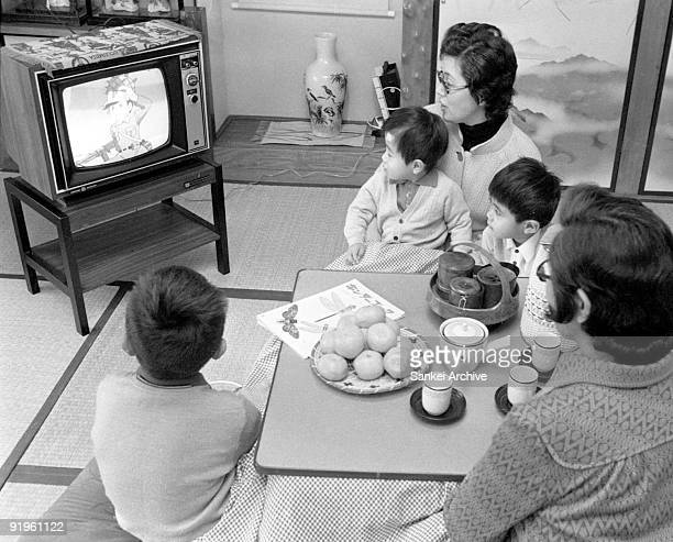 People watch a television sitting under kotatsu Japanese small table with an electric heater on December 21 1971 in Japan
