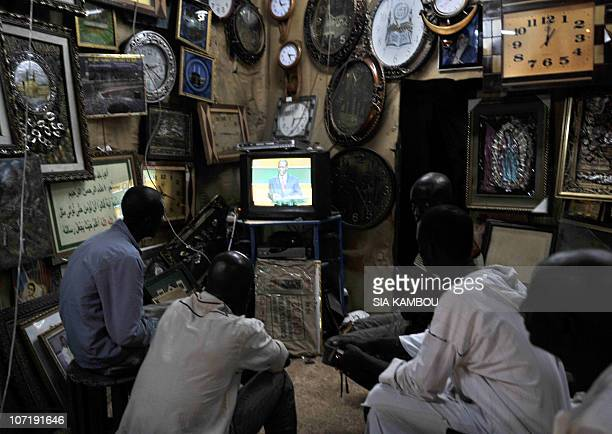 People watch a TV on November 25 2010 in Abidjan showing former Prime Minister Alassane Ouattara during a televised debate with rival Ivorian...