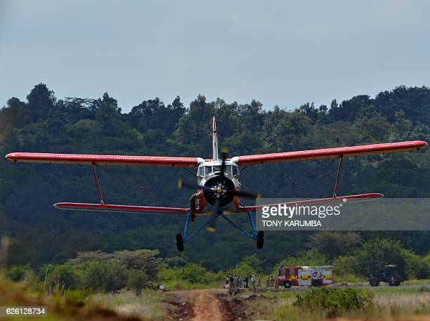 People watch a vintage biplane flying at a low altitude over the Nairobi National Park in Nairobi on November 27 2016 as part of of a crossAfrica...