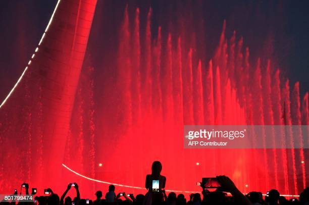 People watch a water and light show in Sochi on June 26 2017 on the sidelines of the 2017 FIFA Confederations Cup football tournament in Russia / AFP...