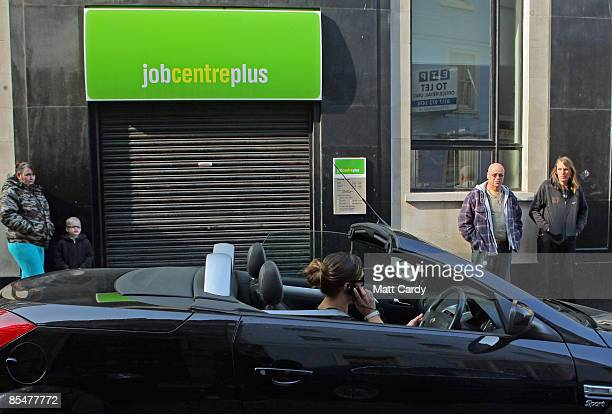 People watch a woman speaking on her mobile phone as she drives her convertible sports car past a Job Centre on March 18 2009 in Bristol England...