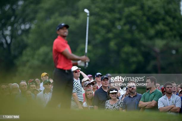 People watch after Tiger Woods of United States bitt from the 9th tee during the fourth round of the US Open at Merion Golf Club on June 16 2013 in...