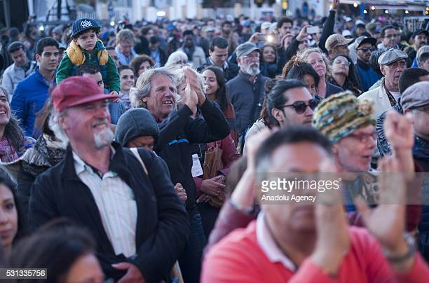 People watch American free jazz bassist Jamaaladeen Tacuma's performance during 19th Annual Gnaoua Music Festival at Moulay Hassan square in...