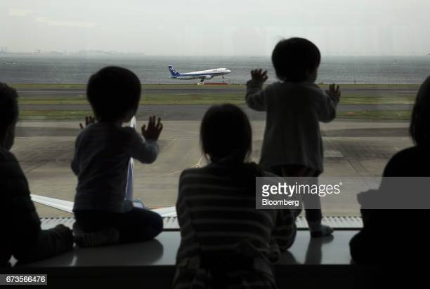 People watch an All Nippon Airways Co aircraft taking off at Haneda Airport in Tokyo Japan on Wednesday April 26 2017 ANA is scheduled to release...