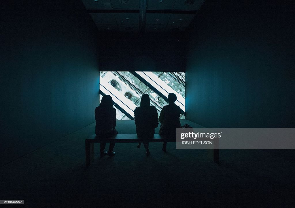 People watch an art piece entitled 'Shadow Sites II' inside the San Francisco Museum of Modern Art (SFMOMA) in San Francisco, California on April 28, 2016. The newly redesigned museum integrates a 10-story expansion in a new building and will open to the public on May 14, 2016. / AFP / Josh Edelson / RESTRICTED