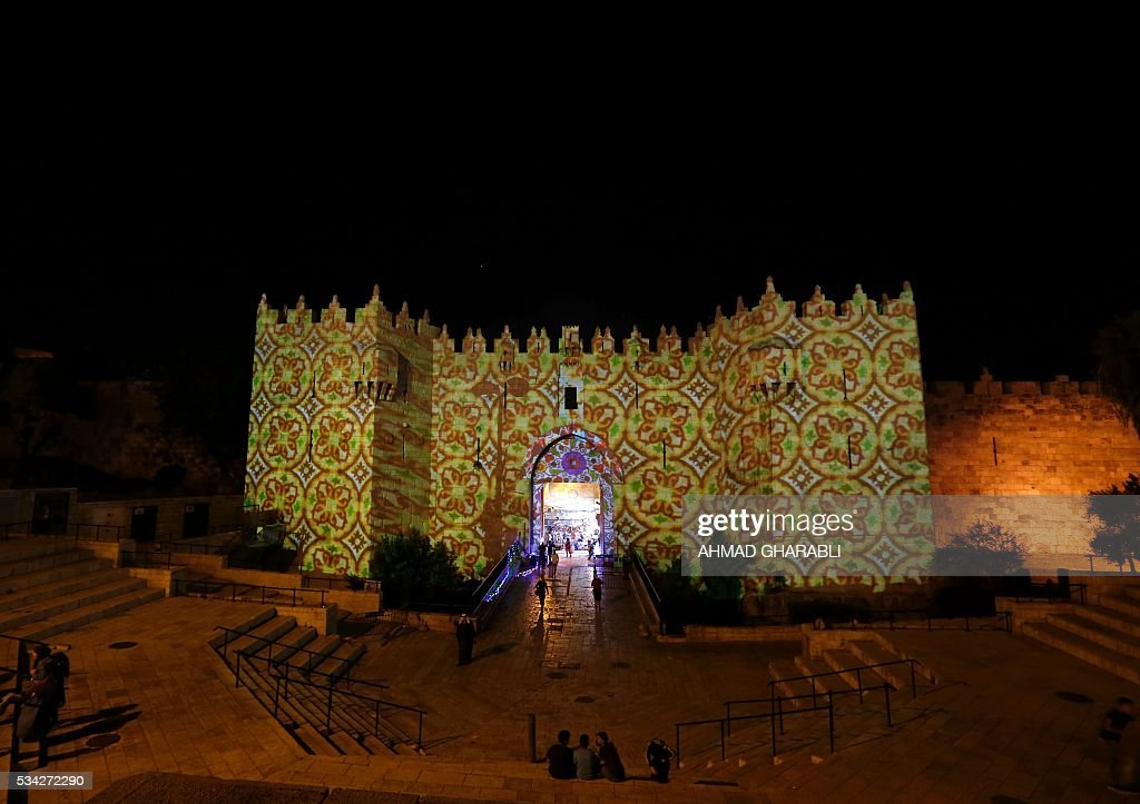 People watch an audiovisual light show projected over the ancient walls of Jerusalem's Damascus Gate in the old city during the Festival of Lights on May 25, 2016. / AFP / AHMAD