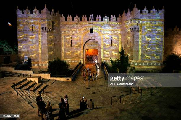 People watch an audiovisual light show projected over the ancient walls of Jerusalem's Damascus Gate in the old city during the Festival of Lights on...