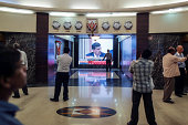 People watch an electronic screen showing television coverage of Raghuram Rajan governor of the Reserve Bank of India speaking during a news...